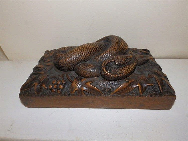 A large carved wood paperweight with serpent and iv