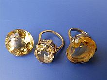 Two citrine rings together with a loose cut stone. (3)