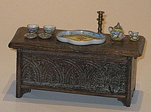 A miniature oak Coffer with a teaset and a candlestick
