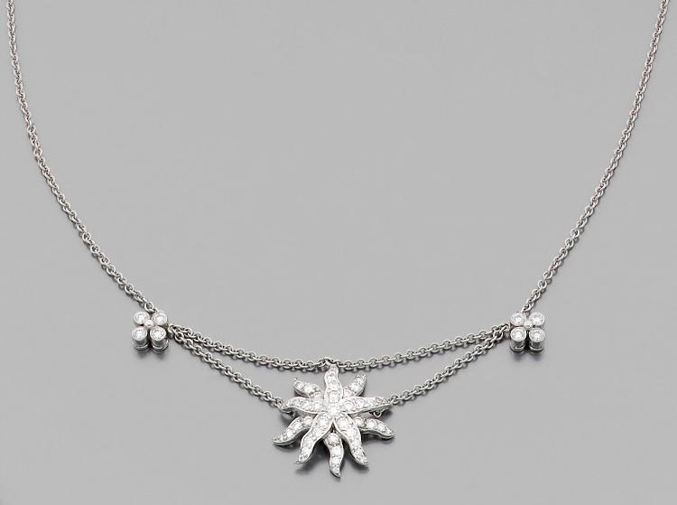 TIFFANY & CO Collier  en platine, centré d'un soleil de diamants retenu entre deux étoiles serties de diamants.Signé.Longueur : 40 cm environ. Poids : 11 g. A diamond and platinum necklace by Tiffany & Co.