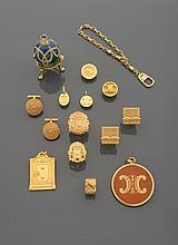 CELINE, BALENCIAGA... Lot en métal doré comprenant: deux paires de boutons de manchettes (l'une signée Balenciaga), un porte-clés, quatre pendentifs siglés Céline, deux boutons Céline, une bague jonc ouverte, deux éléments siglés Céline, un oeuf en