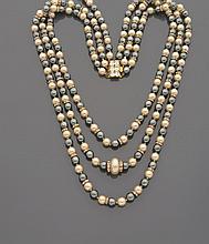 CELINE Collier asymétrique en trois rangs de perles d'imitation blanches et grises, viroles pavées de strass, le deuxième rang centré d'une perle blanche plus importante.    Monogrammé