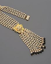 CELINE Sautoir en cinq rangs de perles d'imitation blanches, centré d'une tête de lion en métal doré et pavé de strass retenant un pompon de douze rangs de perles d'imitation terminés par une viroles pavée de strass et une perle de verre noir. Non