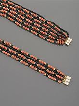 CELINE Ensemble de deux colliers en métal doré, à trois rangs de perles de verre orangé et noir alternées de viroles pavées de strass et deux rangs de perles de verre noir facetté.    Un tour de cou et un collier long.    Non signés