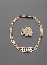 Collier en métal doré, pavé de strass et centré d'un motif à cinq strass de taille navette.     Accompagné d'une broche éléphant en métal doré pavée de strass et de pierres de couleur.    Monogrammée