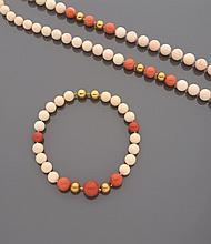 Long collier en chute de perles de verre imitant le corail blanc, alterné aux deux extrêmités de perles imitant le corail rouge et perles de métal doré.    Accompagné d'un bracelet à l'identique