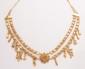Collier draperie en or jaune, formé de deux rangs de course d'étoiles réunis au centre par une fleur d'or jaune filigrané, des breloques pendant sur le rang inférieur.       Poids : 28,4 g.      An 18K gold necklace.