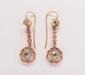 Paire de pendants d'oreilles en vermeil, en ligne de petits diamants tables retenant un diamant taillé en rose plus important.       Epoque XIXe.       Poids : 5,8 g.      A pair of 19th Century diamond and vermeil ear pendants.