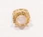 Bague en fils d'or jaune, figurant une fleur aux pétales d'or jaune amati, le caeur orné d'un cabochon de pierre de lune.       Poids : 9,6 g.       A moonstone and 18K gold ring.