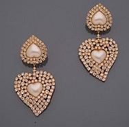 ESCADA        Paire de pendants d'oreilles en métal doré, un coeur en perle d'imitation dans un entourage de strass retenant en pampille un second coeur plus important.   Signés.     Longueur : 10,3 cm environ. (accident)