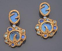 Yves SAINT LAURENT        Paire de pendants d'oreilles en métal doré figurant deux importants strass bleus sertis clos dans un branchage en métal doré, dans un entourage de strass bleus plus petits.    Signés.    Dimensions : 9 x 5 cm environ