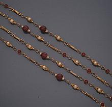 CHANEL        Sautoir en métal doré alternant perles d'imitation, perles godronnées de verre rouge et strass rouge.     Années 1950.     Longueur : 200 cm environ.