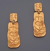 Christian LACROIX Paire de boucles d'oreilles en métal doré, une plaque gravée d'un soleil retenant une plaque plus importante gravée d'une croix, d'un croissant de lune et d'une étoile. Signées. Dans sa boîte. Dimensions : 8,2 x 2,8 cm environ.