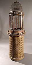 Cage en bois peint affectant la forme d'un donjon appareillé de pierres en trompe l'aeil.  Le dôme, ceinturé et coiffé d'une balustrade, est ajouré d'une grille en fer forgé ponctuée de colonnes.  Vers 1800 - 1820  Hauteur : 255 cm