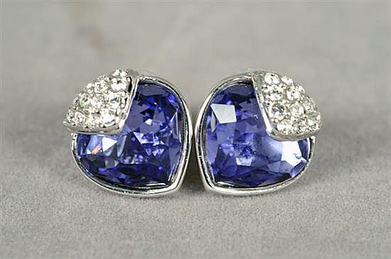 Par de aretes. Swarovski. Diseño con cristales púrpuras y blancos. Incluye certificado. Peso: 5.7 grs.