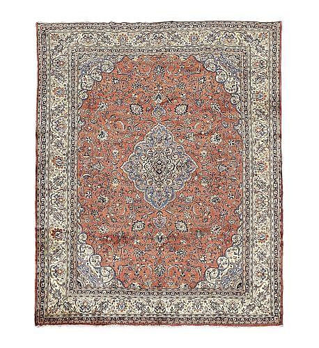 Alfombra iraní. Estilo Sarouk. En lana, anudada a mano. Diseño floral con medallón central a manera vegetal, en tonos naranja y marfil.