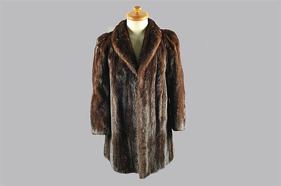 Abrigo para dama. Elaborado en piel de mink, en tono marrón oscuro. Diseño con dos bolsillos exteriores. Talla chica.