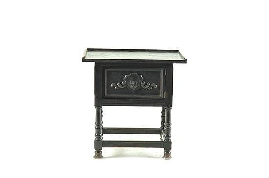 Mesa de noche. Estilo colonial. Elaborada en madera tallada color negro. Soportes torneados y una puerta central.