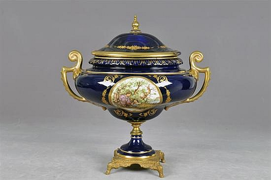 Tibor. Origen italiano. En porcelana, en color azul cobalto con esmalte dorado y base de metal decorado. Decoración vegetal y floral.