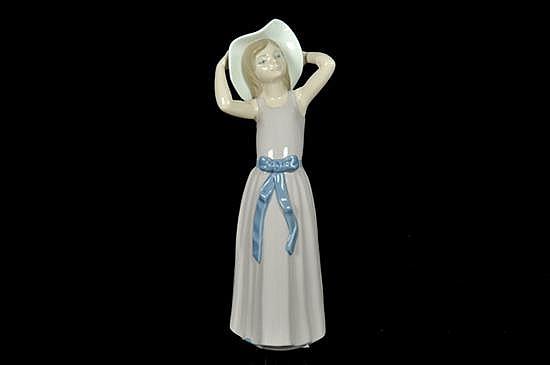 Niña con vestido y sombrero. Figura de porcelana Lladró. Acabado brillante. Muy buen estado de conservación. Altura: 26 cm.