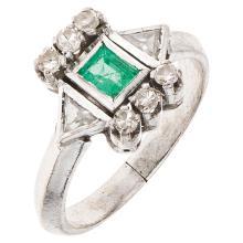 A palladium silver ring with 1 rectangular cut emerald ~0.20 carats and 8 diamonds.