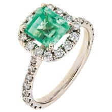 A 14K white gold ring with 1 emerald cut emerald ~1.60 carats and 34 brilliant cut diamonds.
