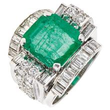 An 18K white gold ring with 1 emerald cut emerald ~6.0 carats, and 50 brilliant and baguette cut diamonds.