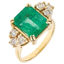 An 18K yellow gold ring with 1 emerald cut emerald ~3.90 carats and 6 brilliant cut diamonds.
