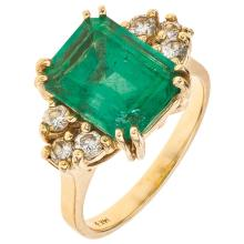 An 18K yellow gold ring with 1 emerald cut emerald ~4.20 carats and 6 brilliant cut diamonds.