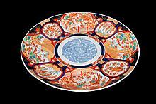 Platón. En porcelana policromada. Con bordes azul cobalto. Decorado con motivos florales y vegetales sobre fondo rojo.