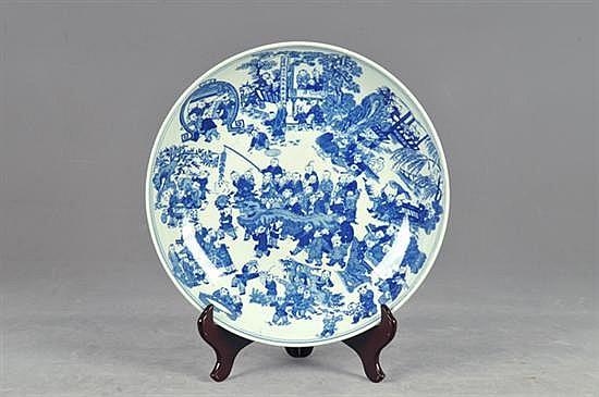 Platón. Origen chino. En porcelana, color azul cobalto. Diseño circular. Con base. Decorado con escena de festival. Dimensiones: 8 x 40