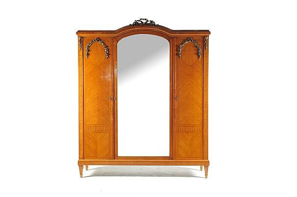 Armario. Estilo Imperio. En madera tallada y enchapada de encino. Con 3 puertas abatibles (con espejo biselado) y espejos interiores.