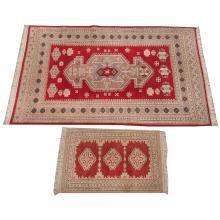 Lote de alfombra y tapete. Siglo XX. Consta de: a) Alfombra anudada a mano en lana y algodón, de fondo rojo y motivos geométricos. Otra