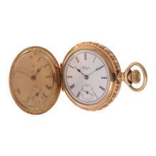 Reloj de bolsillo. Marca Elguin. Caja circular de chapa con motivos florales. Corona de cebolla. Carátula blanca con índices romanos.