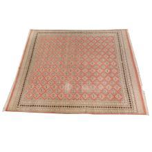 Alfombra geométrica. Siglo XX. Anudada a mano en fibras de lana y algodón. Diseño simétrico, decorada con motivos romboidales.