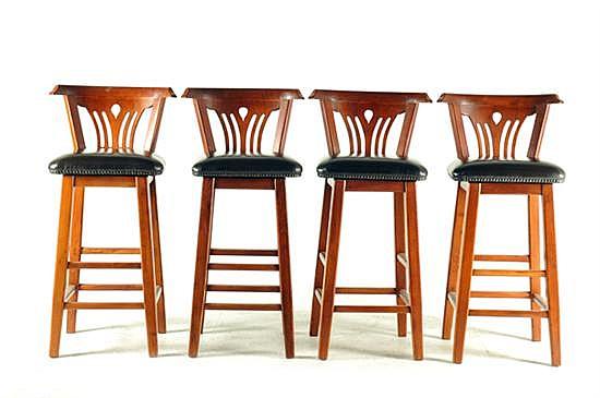 4 Sillas altas. En madera tallada. Diseño con respaldo curvo y calado, asiento giratorio acojinado en vinilo color café. Piezas: 4