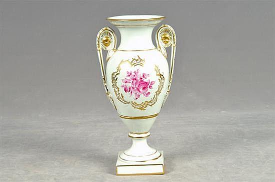 Jarrón. Elaborado en porcelana, acabado brillante. Diseño con esmalte en oro, doble asa. Decorado con motivos florales y mascarones.