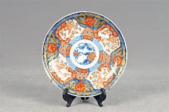 Plato decorativo. Estilo Imary. En porcelana policromada. Diseño oriental; circular con esmalte dorado. Incluye soportes.