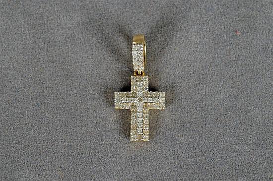 Dije. Elaborado en oro blanco de 14k. Diseño a manera de cruz, con brillantes en corte completo, peso exacto 0.20 Ct. Peso: 0.8 grs.