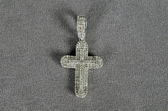 Dije. Elaborado en oro blanco de 14k. Diseño a manera de cruz con bordes redondeados y brillantes en corte completo. Peso: 1.0 grs.