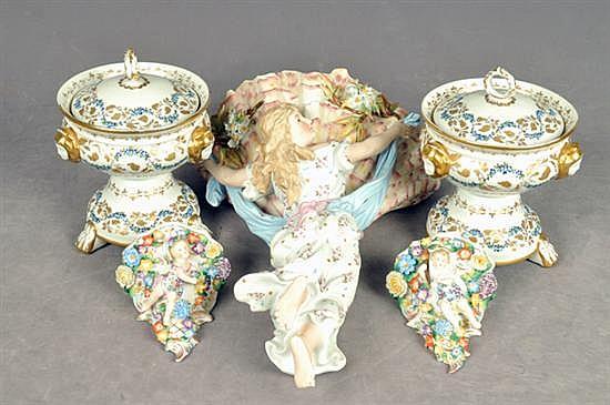 Lote de porcelana. Diferentes tamaños y diseños. Consta de: Figura de mujer con venera, par de peanas y 2 bomboneras. Piezas: 5
