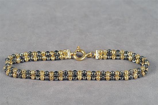 Pulsera. Origen italiano. Elaborada en oro de 14k. Diseño a dos hilos, con boleado a dos tonos. Peso: 8.9 grs.