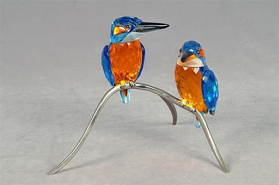 Par de aves. Origen austriaco. En cristal de Swarovski. Diseño facetado con vivos en azul y naranja; con rama y patas metálicas.