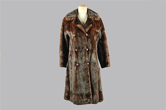 Abrigo corto. Elaborado en piel de mink, tonalidad café. Diseño con botonería de metal dorado entretejida. Talla chica.
