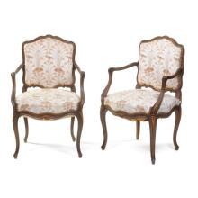 Par de sillones. Francia. Siglo XX. Estilo Luis XV. En madera tallada de roble. Con respaldos y asientos en tapicería floral blanca.