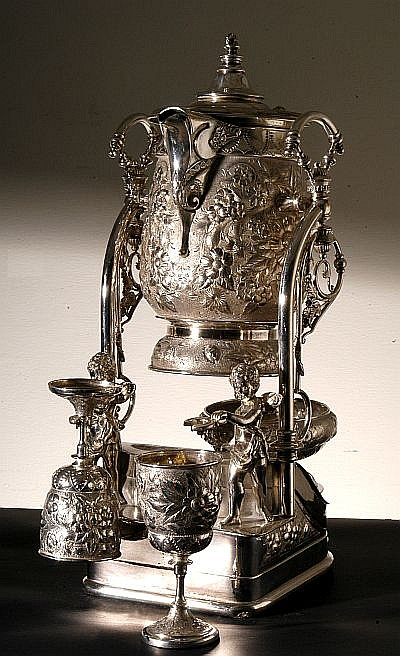 Samovar. De metal plateado. Diseños flores en relieve y figuras de angelitos. Incluye dos copas y tazón. Altura. 57 cm.