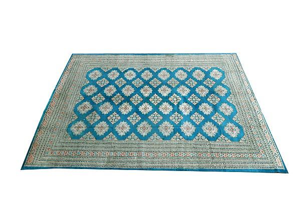 Alfombra. Origen pakistaní. Estilo Boukhara. En lana, anudada a mano. Decorada con motivos geométricos sobre fondo verde y beige.