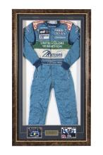 MARK WEBBER: A Sparco 2001 'United Colours of Bennetton' race suit as worn by Mark Webber during his official testing season for his Formula 1 career, with embroidered name to belt, signature to mid section in black ink and name to label, with accompanying CoA issued by Ann Neal (Manager of Mark Webber), presented in shadow box frame, 167cm high x 96cm wide x 9cm deep.
