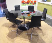 A modern smoke glass pedestal table and six leatherette upholstered swivel chairs
