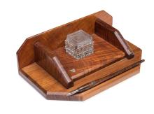 An Art Deco Tasmanian fiddle back blackwood inkstand and pen, with cut glass inkwell and applied map of Tasmania